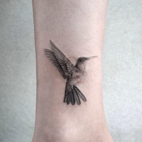 Realistic Black&Grey Humming bird tattoo in Ankle