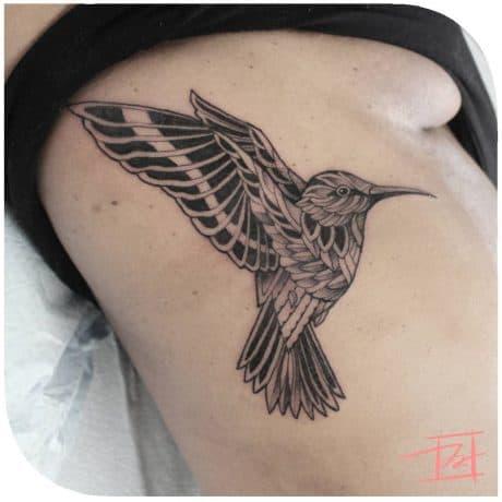Tribal Black Humming bird tattoo in Rib