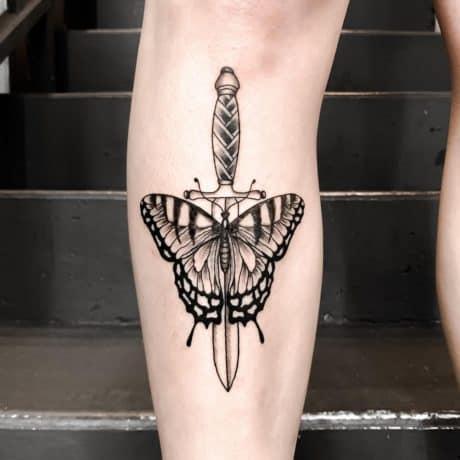 Butterfly dagger tattoo on leg