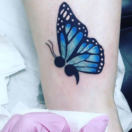 Semi-colon blue butterfly tattoo on leg