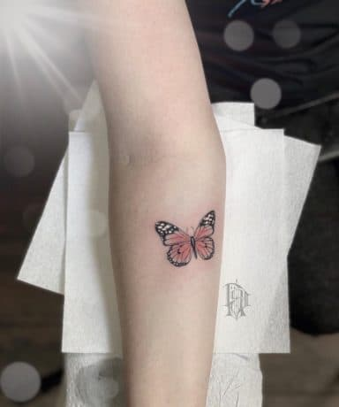 Small Pink butterfly tattoo on arm
